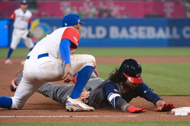 March 17: United States infielder Brandon Crawford dives into third base after hitting a ninth inning triple against Puerto Rico.