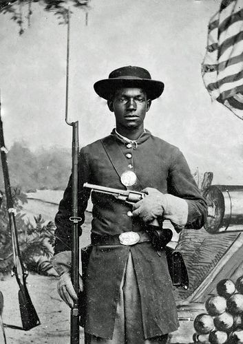 Freedom Fighter | 1865 (Close Up) African American soldier in Union uniform with a rifle and revolver posing in front of painted backdrop with American flag and artillery pieces (close up shot).