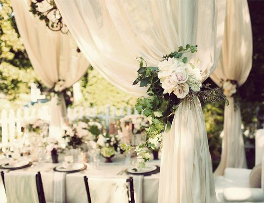 "Plain pole arch swathed in curtains (same as entryway to barn) and floral ""tie-backs"". love this!!"