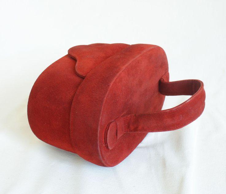 Červený semišový kabelko-kufřík Zajímavá kabelka ve tvaru malého kosmetického kufříku. Je ušita z červeného semiše. Zavírá se na druk v chlopni na přední části. Na vnitřní straně víka je je malé zrcádko. Vnitřní prostor není členěný, je vypodšívkován světle šedou rypsovou podšívkou. Kabelka je velmi zajímavá. Díky své barevnosti a netypickému tvaru ...