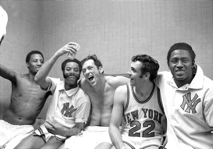 The New York Knicks' starting five -- Dick Barnett, Walt Frazier, Bill Bradley, Dave DeBusschere, and Willis Reed (l. to r.) -- rejoice in the dressing room after winning their fifth playoff game against the Milwaukee Bucks, by a lopsided score of 132-96, and with it their first National Basketball Association Eastern Conference title since 1953. The Knicks went on to beat the Los Angeles Lakers in the finals for their first-ever NBA championship.