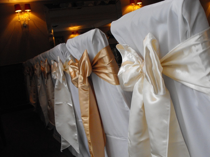 Alternating Ivory and Gold Satin Bows on White Chair Covers
