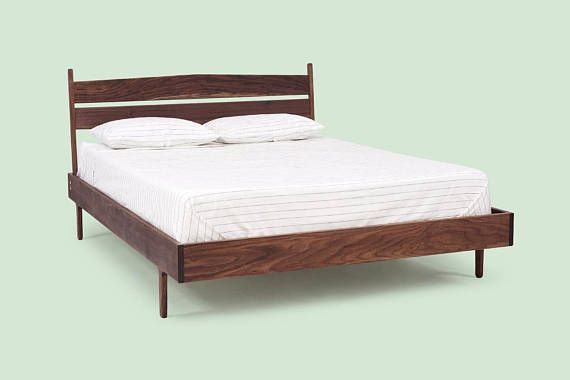 A solid wood bed frame finished with a natural oil-wax blend.