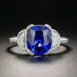 A lush vivid intense blue Ceylon Sapphire, weighing 3.21 carats, radiates between a pair of bright white and sparkling half-moon diamonds (.48 ct. total weight), all presented in gleaming platinum and accentuated with delicate milgraining in timeless neoclassical style. Sapphires don't get much nicer! Simply stunning. Currently ring size 6. Accompanied by gemological report form Stone Group Laboratory stating: Indications of thermal enhancement, Ceylon origin.