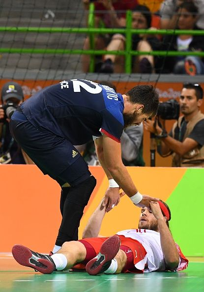 France's pivot Luka Karabatic helps Denmark's left back Mikkel Hansen get up…