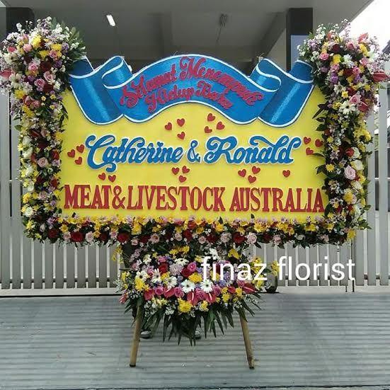 Bunga Papan Pernikahan yang kami tampilkan kali ini cukup cantik dan arsistik. Berukuran 2m x 1,25m dengan bunga kepala di sudut kiri-kanan dan menjuntai hingga menyerupai lis bunga, kami Toko Bunga Finaz, Toko terkenal TOKO BUNGA MURAH di Jakarta merasa tertantang untuk memberikan model-model yang menarik dan penuh seni. Jangan ragu, segera pesan ke kami, TOKO BUNGA DI JAKARTA.