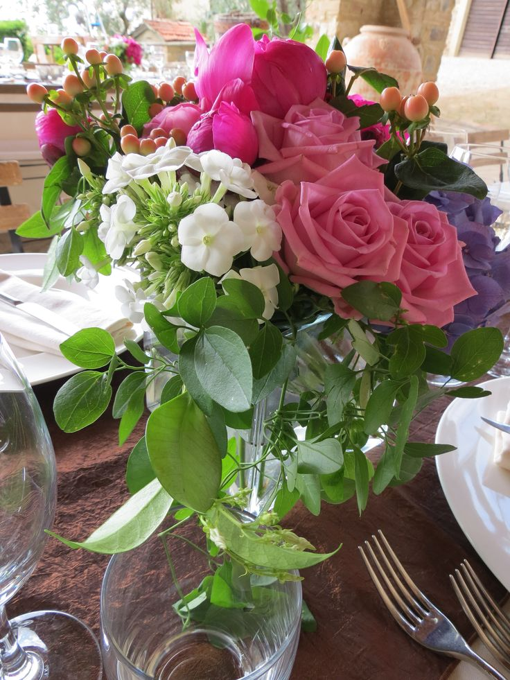 Square glass vases with fuchsia peonies, pink roses, pale pink hypericum, blue hydrangea and white phlox. Event Planner : Wedding Italy.