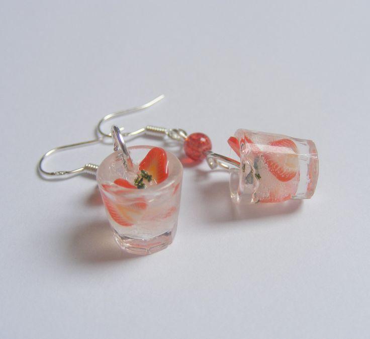 Refrescante cóctel de fresa que tiene rebanadas de fresa, hojas de menta y diminutos cubos de hielo