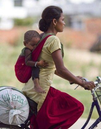 Babywearing mama and child in Nepalgunj, Nepal where bike travel is the usual transportation.