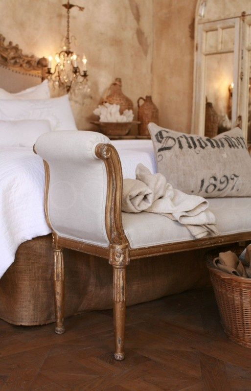 French Bedroom..old mirrored door lean against aged walls reflecting the contract of burlap and white linen bedding...