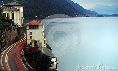 Long exposure photos of a view of Lake Como, between mountains and water at dusk on a beautiful September day. Cars that travel the winding road along the lakeside with their headlights create the features trails yellow and red light