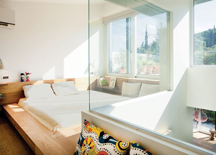 Ritenour carved a window into an L-shaped wall to open the cramped master bedroom to a small, light-filled atrium (below). An unsightly structural beam was covered with wood to create a distinctive sunken bed.