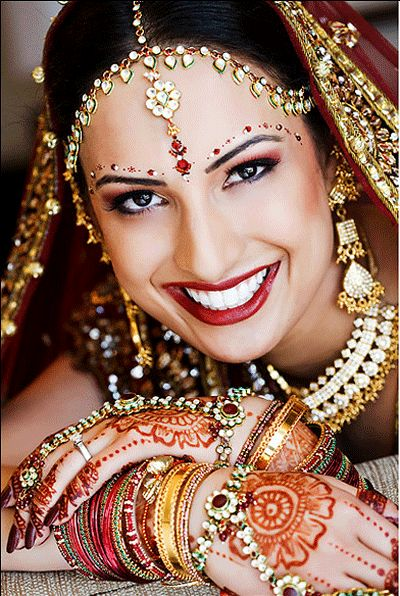 Indian bride wearing an elegant maang tikka with two side strings to cover the forehead also