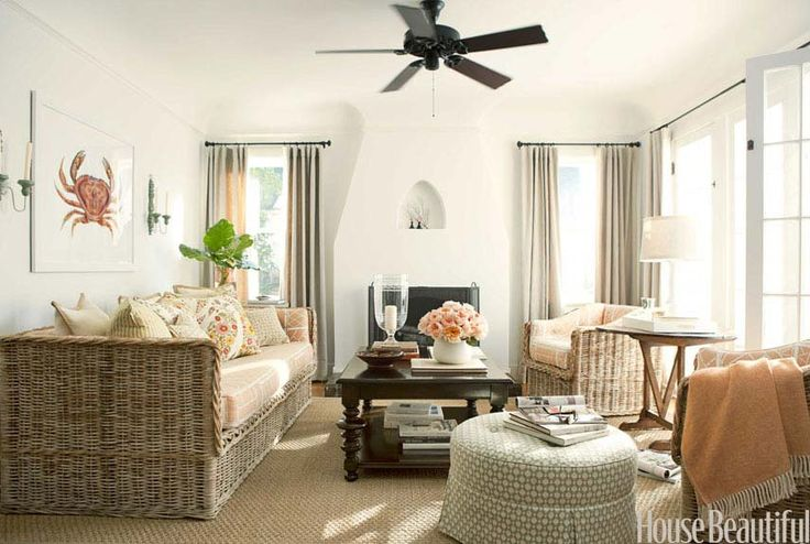 """To give the living room an air of casual elegance, Reid furnished it with """"unpretentious"""" wicker pieces, and she painted the walls Benjamin Moore's White Dove """"to convey a lightness of spirit."""" Adding a pretty punch: garden pinks and pale greens on cushions in Kent-Bragaline Chinese Lattice, and an ottoman covered in Celerie Kemble's Betwixt for Schumacher. Greek key hurricane from Hollyhock. Tamara Clark crab print.   - HouseBeautiful.com"""