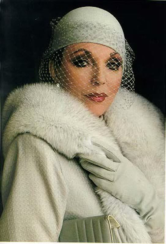 Joan Collins elegant hat veil over her face..she always dresses to the 9's