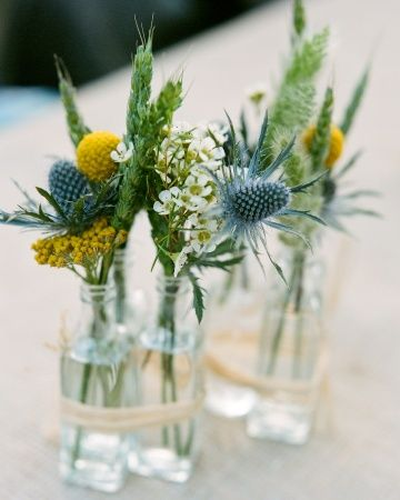 Burlap and small glass vases filled with a few flower sprigs topped these reception tables