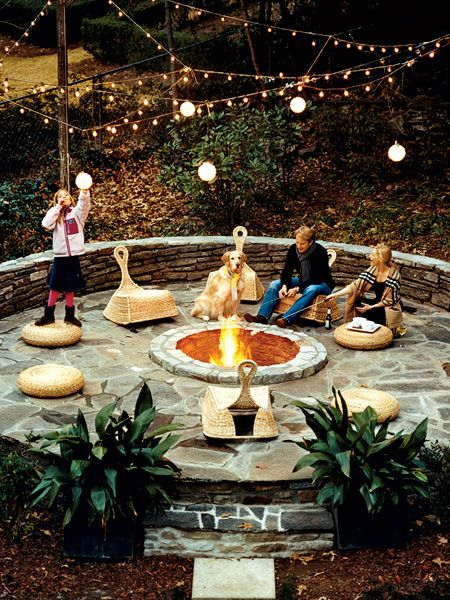 Backyard Fire Pit.  Circular stone fire pit in an Atlanta backyard.  Stone patio surrounding pit ensures plenty of seating.  Love lights strung overhead.  Would want comfier seating.  *Maybe include built in bench with padded seating & pillows along wall that surrounds.