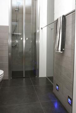 Douche in compacte moderne badkamer. De gasten badkamer in het penthouse heeft een klein oppervlakte. Door de douchecabine 'buiten' de badkamer zelf te plaatsen wordt er aan ruimte gewonnen. De mooie grote vloertegels zorgen ook voor een extra ruimtelijk gevoel. De blauwe ledverlichting zorgt niet alleen voor sfeer maar zorgt er ook voor dat je niet al het licht hoeft aan te zetten als je de badkamer wilt gebruiken. MD Design