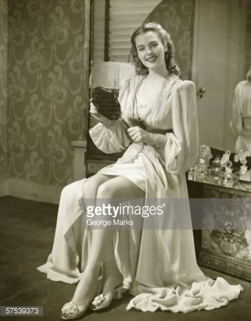 Stock Photo : Young woman holding mirror, sitting at dresser, (B&W)