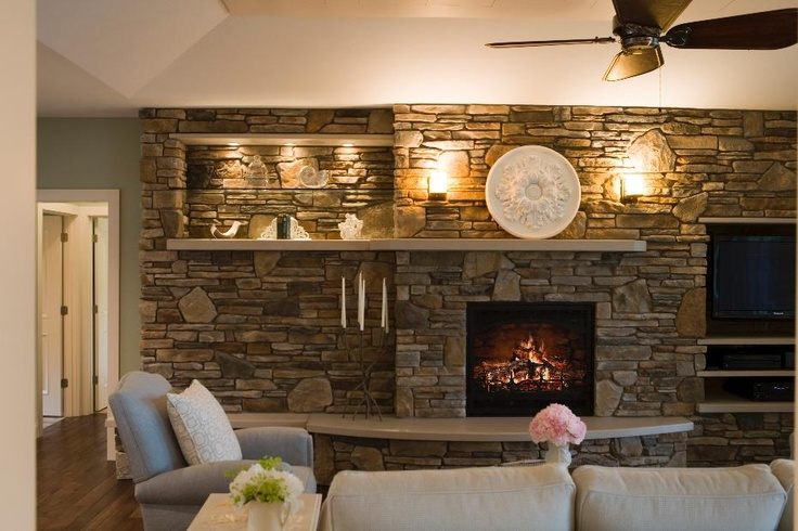 This stone wall has it all- fireplace, shelving and ...