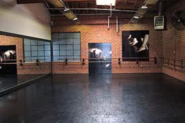 home dance studio with black floor and ballet barre