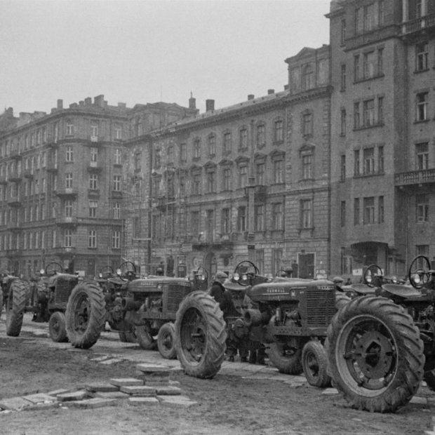 Zdjęcie z 1946 r. Widać na nim amerykańskie traktory Farmall firmy Case, dostarczone do Polski w ramach pomocy UNRRA. Przypłynęły statkiem do Gdyni, potem transportowane były do gospodarstw na południu kraju. Po drodze miały przystanek w Warszawie, w Alejach Jerozolimskich, obok zburzonego Dworca Głównego. Stoją na tle istniejących do dziś kamienic między ulicami Poznańską i Emilii Plater.
