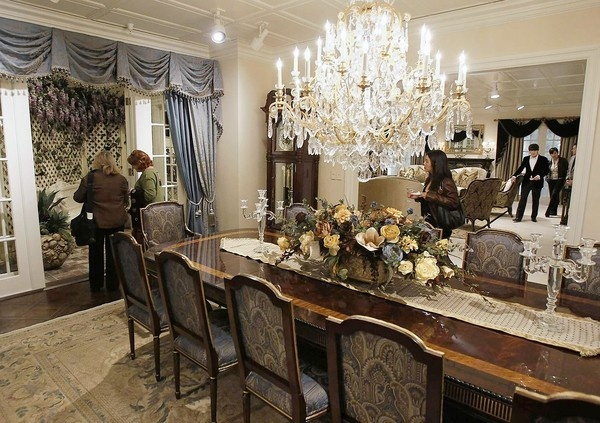 Daily Pilot Newspaper - Guests browse the formal dining room during the grand opening of Marc Pridmore Designs in Costa Mesa on Thursday.  E.J. Victor Dining table and chairs with a Schonbek Chandelier overhead