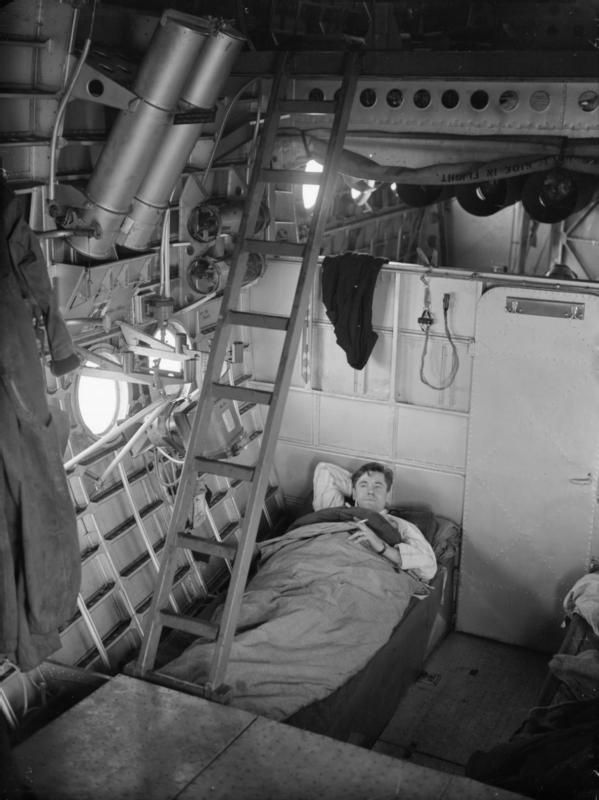 Sergeant Patrick McCombie, a flight engineer of the Royal Australian Air Force, in his bunk on board a Short Sunderland of No. 10 Squadron RAAF at Mount Batten, Plymouth, Devon.