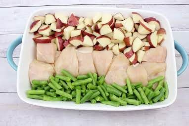 Placing cut up chicken, green beans, and potatoes in a baking dish.