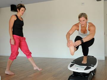 Catch a wave indoors with SURFset in Barrie - Ann Green, right, shows Connie White a few moves on a surfboard at Bliss Ann Green Yoga, which is offering SurfSet yoga classes for beginners and yoga pros.