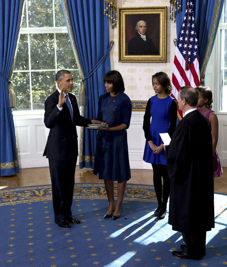 President Barack Obama is officially sworn-in by Chief Justice John Roberts, not pictured, in the Blue Room of the White House during the 57th Presidential Inauguration in Washington, Sunday Jan. 20, 2013, as first lady Michelle Obama, holds the Robinson Family Bible, as daughter Malia and Sasha watch. (AP Photo/The New York Times, Doug Mills, Pool)