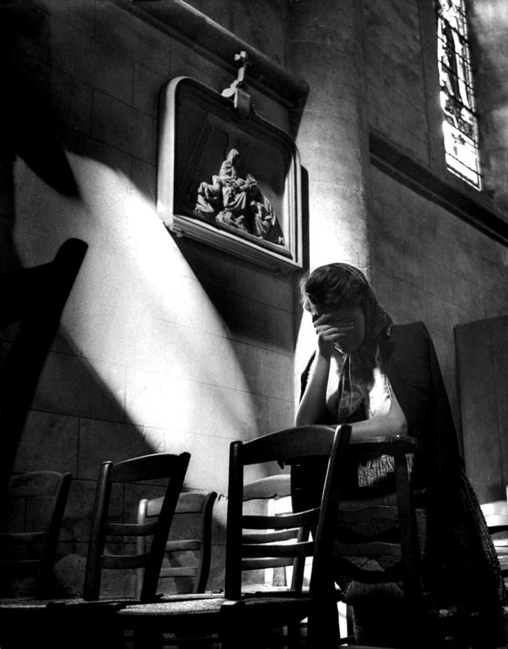 A French woman prays  in a church following the Battle of Cherbourg. The Battle of Cherbourg was part of the larger Battle of Normandy and was fought immediately after the successful Allied landings on 6 June 1944 in France. American troops isolated and captured the fortified port, which was considered vital to the campaign in Western Europe, in a hard-fought, month-long campaign. France. July 1944. Image taken by David E. Scherman