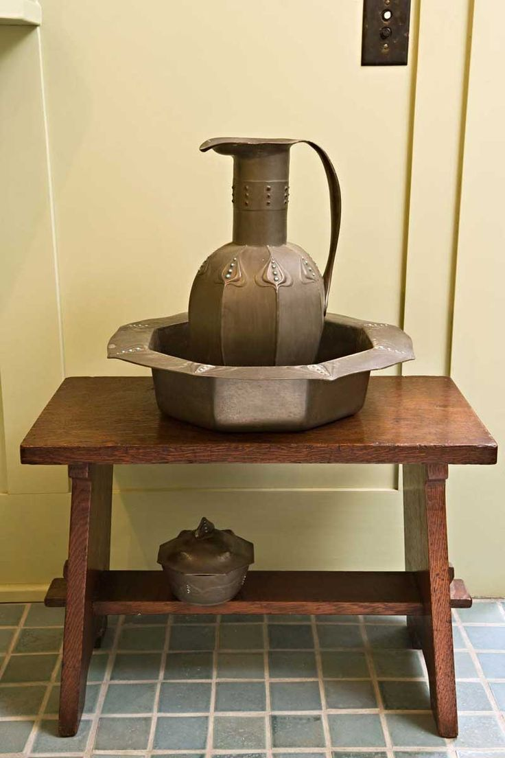 The Osiris Pewter jug by George Logan sits n a 1902 Gustav Stickley bench