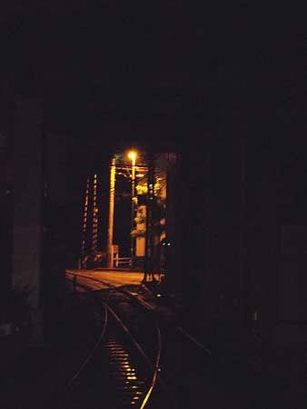ビルの下から抜けてゆく。橙色に光る夜の踏切、向こうの風景へと続く線路。[2011/8 高松琴平電気鉄道志度線瓦町駅]© 2010 風旅記(M.M.) 風旅記以外への転載はできません...