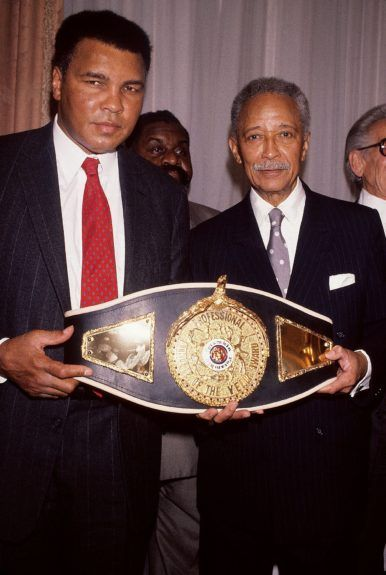 <p> Three time heavyweight boxing champion Muhammad Ali is given the first ever Victor Potamkin award belt by Mayor David Dinkins in 1992 in New York (Frederick Watkins, Jr./Ebony Collection)</p>
