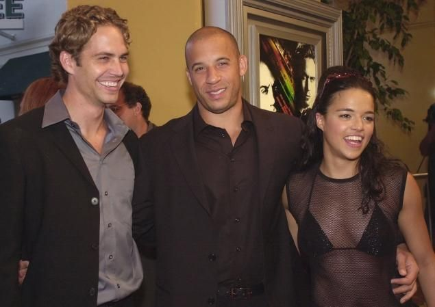 """The Fast and the Furious"" cast members Paul Walker, Vin Diesel and Michelle Rodriguez (left to right) arrive at the world premiere of the film on June 18, 2001, in Los Angeles. The franchise had seven total films."