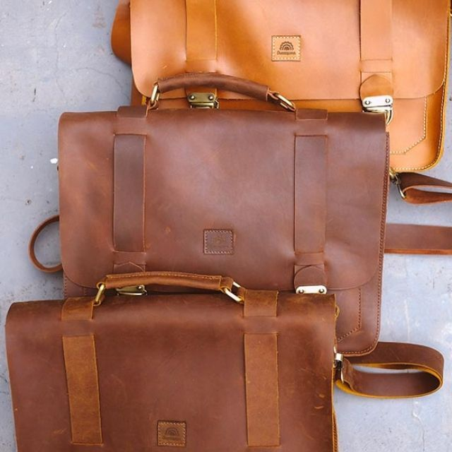 - MATERIAL: cowhide leather - CLOSURE: 2 buckle flap, zippers - HANDLES: Top grab handle - STRAPS: Detachable and adjustable strap with shoulder pad - INTERIOR DETAILS: 2 compartements, 2 slip pockets - INTERIOR MATERIAL: Suede fabric - HARDWARE: Antique brass