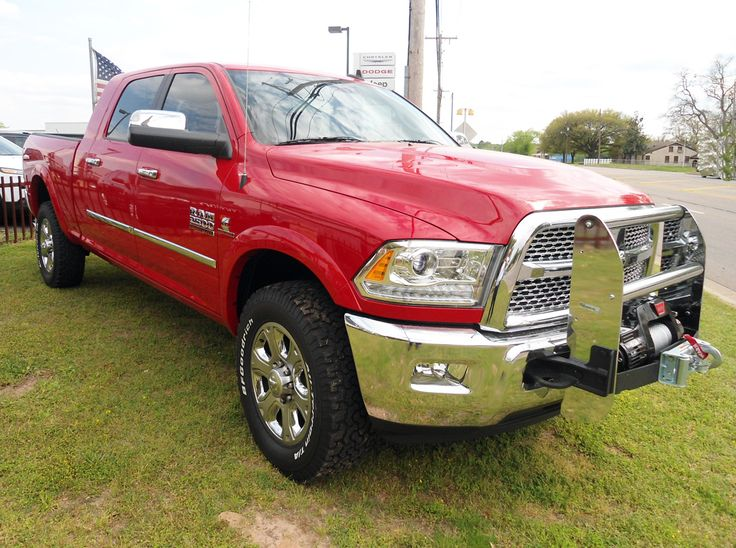 2014 Ram 2500 Laramie Mega Cab 4X4 accessorized with a Warn Winch and Grille Guard, AMP Power Steps, Spray in Bedliner, 20-inch tires and a Spray in Bedliner. #ramtrucks #truckaccessories