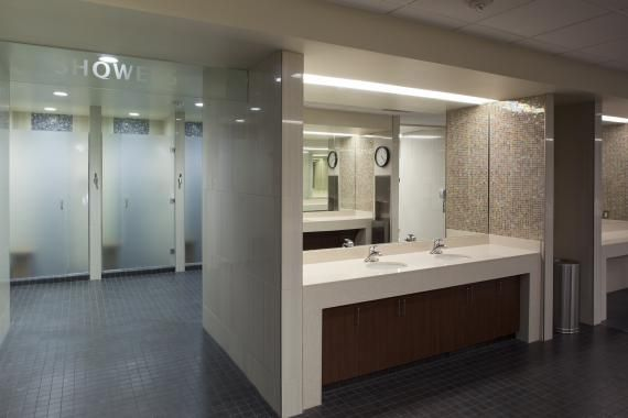 In the locker rooms, each shower stall was increased in size and full glass doors were added for more privacy. Vanity areas have solid-surface tops and aprons. Artisan glass mosaics were added to the interior of the vanity areas. Photo: Ralph Cole Photography