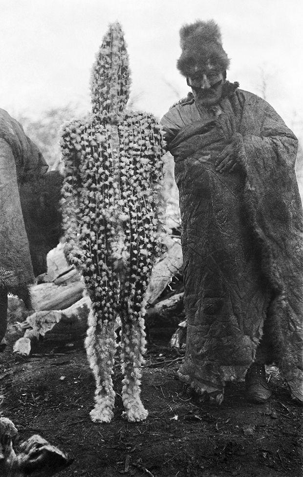 Ein Schamane präsentiert den Frauen K'ternen, das Baby der Erdgöttin Xalpen. K'ternens Körper ist mit rotem Ocker bemalt und mit Daunen bedeckt, Selk'nam (Onas), Tierra del Fuego, Argentina, 1923, photo: Martin Gusinde.