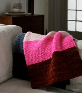 Super Easy Lap Blanket - Curl up with this Super Easy Lap Blanket. Knit with the garter stitch, this colorful afghan pattern is perfect for anyone who wants to learn how to knit a blanket that is sure to keep them nice and toasty during the winter months. This is one of the best beginner knitting projects for those who are looking for something they can work on all throughout the snowy season.