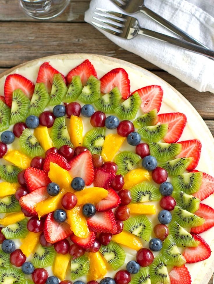 This simple fruit pizza is beautiful and delicious! A soft sugar cookie crust with a cream cheese frosting and topped with sliced fruit.   pinchofyum.com