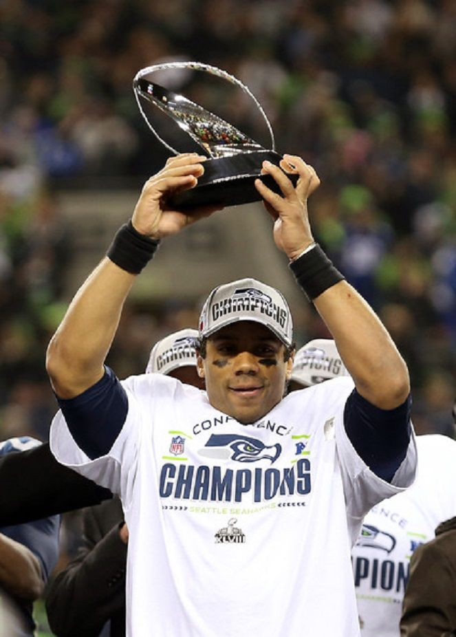 Quarterback Russell Wilson #3 of the Seattle Seahawks celebrates with the George Halas Trophy after the Seahawks defeat the San Francisco 49ers 23-17 in the 2014 NFC Championship at CenturyLink Field in Seattle, Washington.