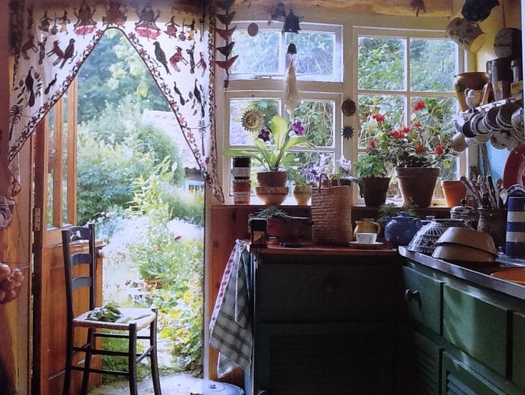 Kitchen with Indian textiles and rustic cabinetry, adjoining a cozy herb garden. From Romantic Country Style book (Victoria Magazine)