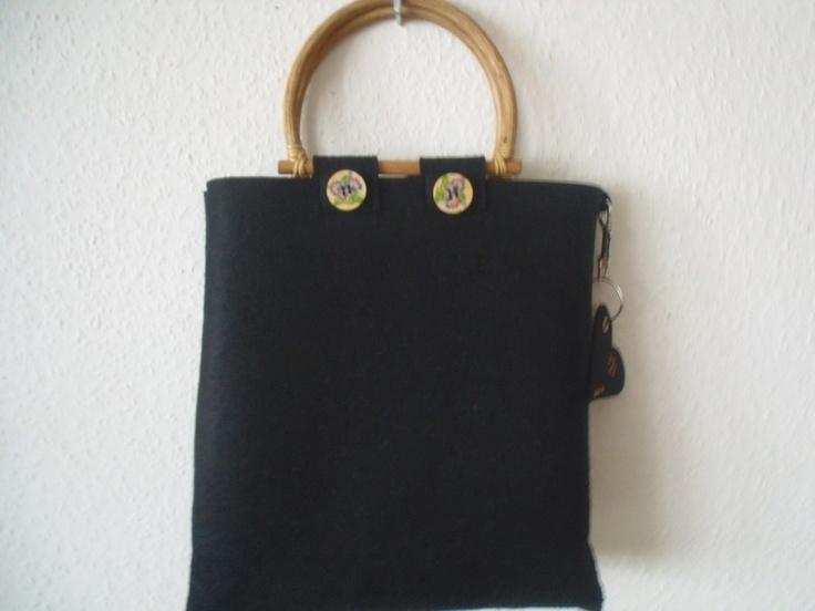Schwarze Filztasche mit Bambusgriffen, verziert mit Knöpfen im dezenten Blumenmuster, an der Seite an einem Karabinerhaken das Markenzeichen von MMD,
