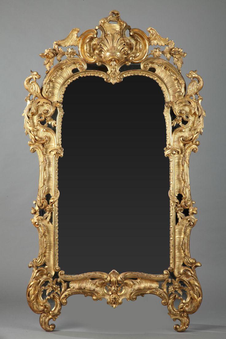 Grand miroir en bois sculpté et doré, orné de d…