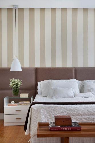 No projeto desse quarto, assinado por Bianca da Hora, a cama de casal recebeu uma cabeceira composta por placas retangulares almofadadas. No ambiente de tons neutros, a superfície acima do móvel foi revestida por papel de parede com listras
