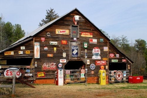 "Pickens, South Carolina This colorful barn is located on Red Hill Road near Pickens. It is often referred to as the ""sign barn"" because of the large collection of old advertisements and signs posted on its exterior."