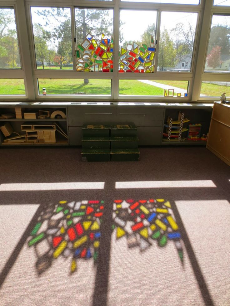 Building with colored blocks next to the window @ SAND AND WATER TABLES