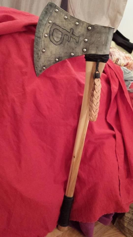 He needed a walking stick but wanted something more subtle.  So..he made a leather axe head attached to the walking stick.  The brand was on the hide he cut the head from. .